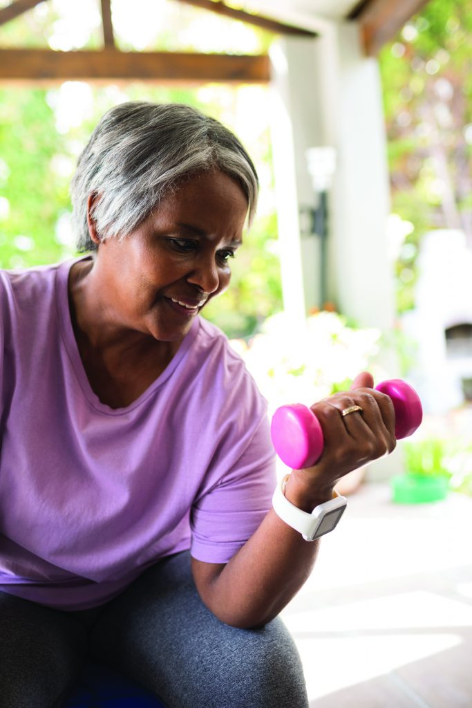 Image of elderly woman lifting a pink dumbbell. Exercise is an important part of the Pritikin Intensive Cardiac Rehabilitation program