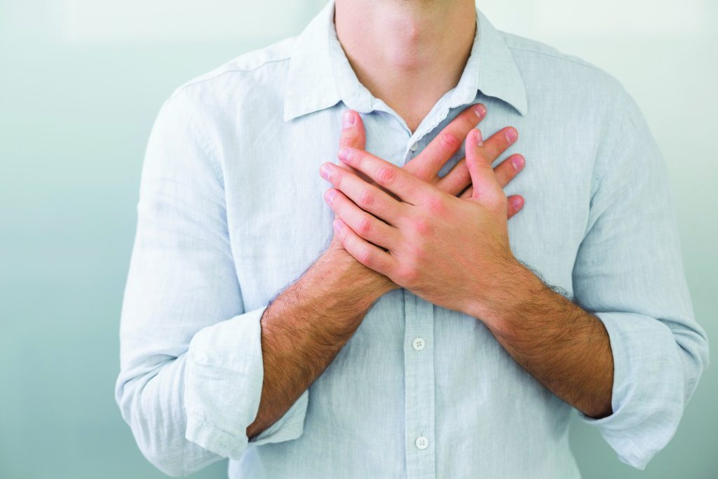 Image of person clutching their chest, as if in pain, see eligibility of joining the Intensive Cardiac Rehab program at North Idaho Cardiac Rehabilitation NICR
