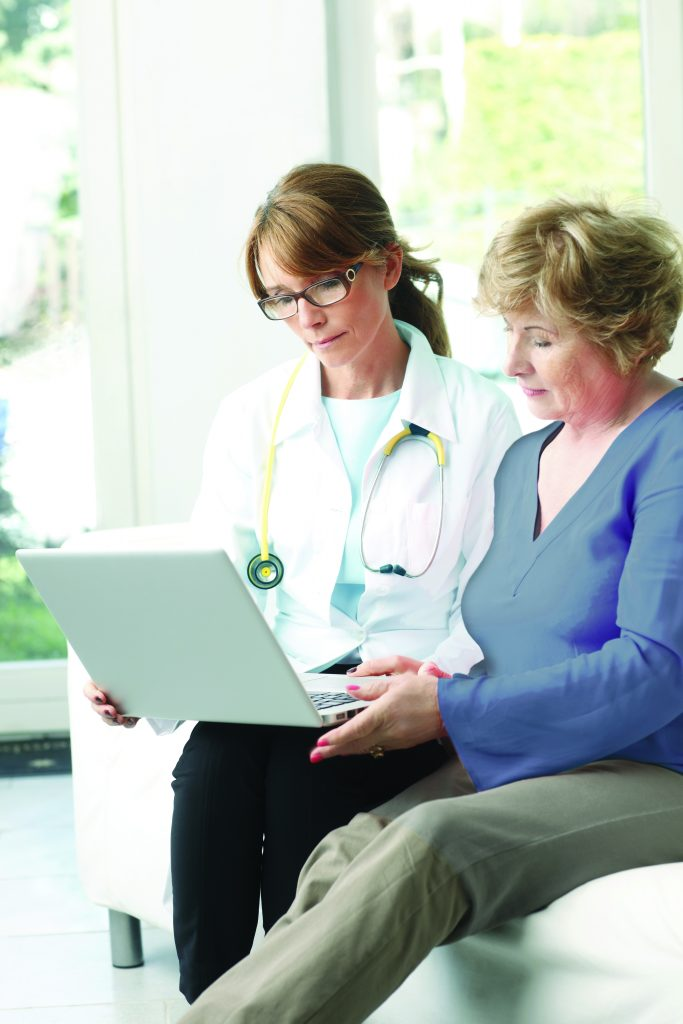 Image of doctor and patient looking at a laptop